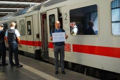 Homem que protesta contra emigrantes no estação de caminhos-de-ferro Fotos de Stock Royalty Free