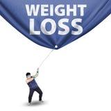 Homem que puxa a bandeira da perda de peso Foto de Stock