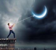 Homem que puxa a lua Imagens de Stock Royalty Free