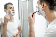 Homem que raspa no banheiro fotografia de stock