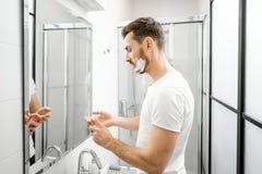Homem que raspa no banheiro fotos de stock