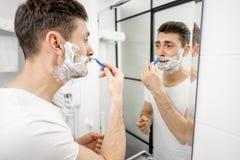 Homem que raspa no banheiro foto de stock royalty free