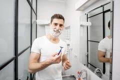 Homem que raspa no banheiro foto de stock