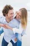 Homem que reboca a mulher na praia Imagem de Stock Royalty Free
