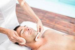Homem que recebe uma massagem facial do massagista fotografia de stock