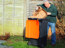 Homem que recicla o lixo ou os desperdícios nos escaninhos Imagens de Stock
