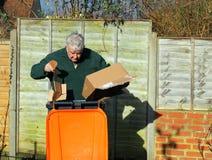 Homem que recicla o lixo ou os desperdícios nos escaninhos Imagem de Stock Royalty Free