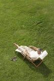Homem que reclina no gramado no livro de leitura da cadeira de plataforma fotos de stock royalty free