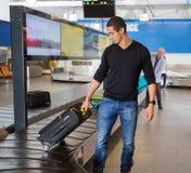 Homem que recolhe a bagagem na correia transportadora no aeroporto Fotos de Stock Royalty Free