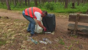 Homem que recolhe garrafas plásticas em torno do escaninho waste video estoque