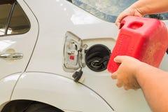 Homem que reenche o carro com cartucho da gasolina foto de stock royalty free