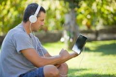 Homem que relaxa com PC da tabuleta Fotos de Stock