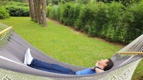 Homem que relaxa e que sorri na rede, jardim do verão com a rede de suspensão para o abrandamento em férias vídeos de arquivo
