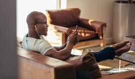 Homem que relaxa em casa a escuta a música imagens de stock royalty free