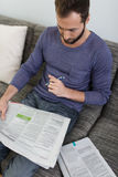 Homem que relaxa em casa lendo um jornal Fotos de Stock Royalty Free