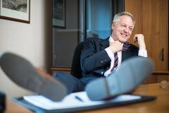 Homem que relaxa em seu escritório após o trabalho Imagens de Stock