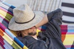 Homem que relaxa em uma rede no por do sol Imagem de Stock Royalty Free