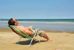 Homem que relaxa na praia Imagens de Stock
