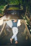Homem que relaxa no ber?o l?quido sobre a angra de fluxo, f?rias que viajam na floresta tropical tropical imagens de stock