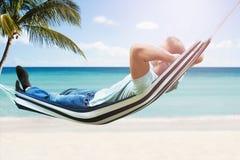 Homem que relaxa no hammock fotografia de stock royalty free