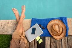 Homem que relaxa perto da piscina com computador fotografia de stock