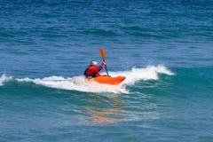 Homem que rema um caiaque do mar Imagens de Stock