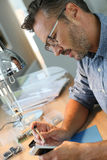 Homem que repara ferramentas do smartphonewith na oficina Imagens de Stock Royalty Free