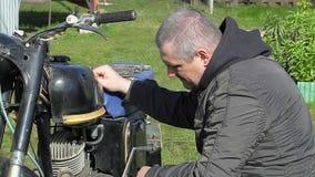 Homem que repara a motocicleta velha em exterior filme