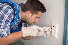 Homem que repara o interruptor da luz em casa foto de stock