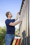 Homem que repara o tapume Fotografia de Stock Royalty Free