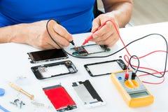 Homem que repara o telefone celular Foto de Stock Royalty Free