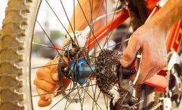 Homem que repara sua bicicleta imagens de stock