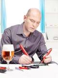 Homem que repara um dispositivo electrónico Fotos de Stock