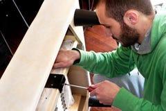 Homem que repara um sofá Fotos de Stock Royalty Free