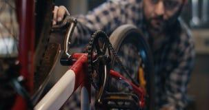 Homem que repara uma bicicleta em uma garagem vídeos de arquivo