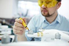Homem que repara zangões na oficina moderna Imagens de Stock