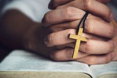 Homem que reza ao deus com uma Bíblia na devoção da manhã imagens de stock