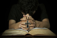 Homem que reza com a Bíblia e cruz Foto de Stock