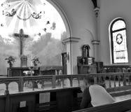 Homem que reza dentro de uma igreja religiosa com vitral e cruz bonitos fotografia de stock