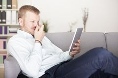 Homem que rir debochadamente a si mesmo como lê sua tabuleta fotos de stock royalty free