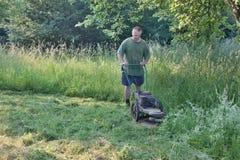 Homem que sega a grama alta Imagens de Stock