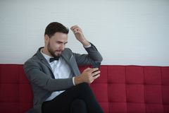 Homem que senta e que usa um telefone esperto imagens de stock royalty free