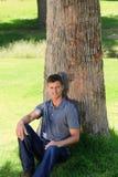 Homem que senta-se ao lado de uma árvore Fotografia de Stock