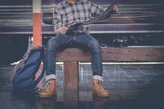 Homem que senta-se com mapa saco do curso no estação de caminhos-de-ferro Foto de Stock Royalty Free