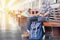 Homem que senta-se com mapa saco do curso no estação de caminhos-de-ferro Imagens de Stock