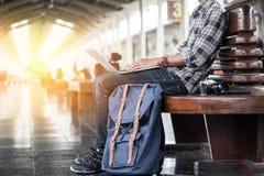 Homem que senta-se com portátil saco do curso no estação de caminhos-de-ferro Imagens de Stock Royalty Free