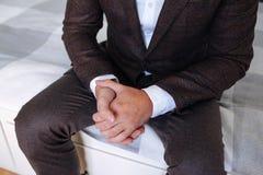 Homem que senta-se com suas mãos cruzadas A mão em um terno marrom, relógio dos homens na mão do homem, a mão de um homem de negó imagem de stock