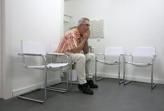 Homem que senta-se e que espera no waitingroom imagens de stock