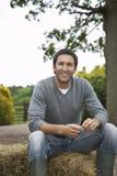 Homem que senta-se em Haybale fora Fotografia de Stock Royalty Free