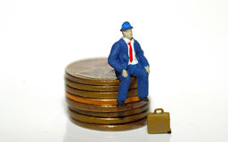 Homem que senta-se em moedas de um centavo imagens de stock royalty free